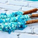 How to Make Frozen Wands (aka chocolate covered pretzel rods) Ingredients Pretzel Rods 1 cup white chocolate melting wafers divided Sprinkles (I used blue and white assorted sprinkles) food coloring (blue) Directions Melt chocolate in microwave according to package directions. Divide the mixture into 2 separate cups and add food coloring to each. ( 1 drop blue for light blue, 2 drops for dark blue) Dip the pretzel rod sticks into the light blue melted chocolate, turning to ensure coverage. Drip the dark blue melted chocolate over the blue chocolate. Place on wax paper and decorate with sprinkles. Let dry.