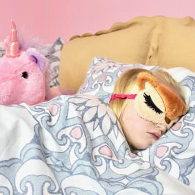 girl sleeping in bed with sleep mask and unicorn